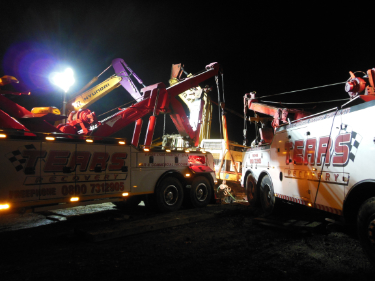 Tears recovering heavy equipment by winch at night